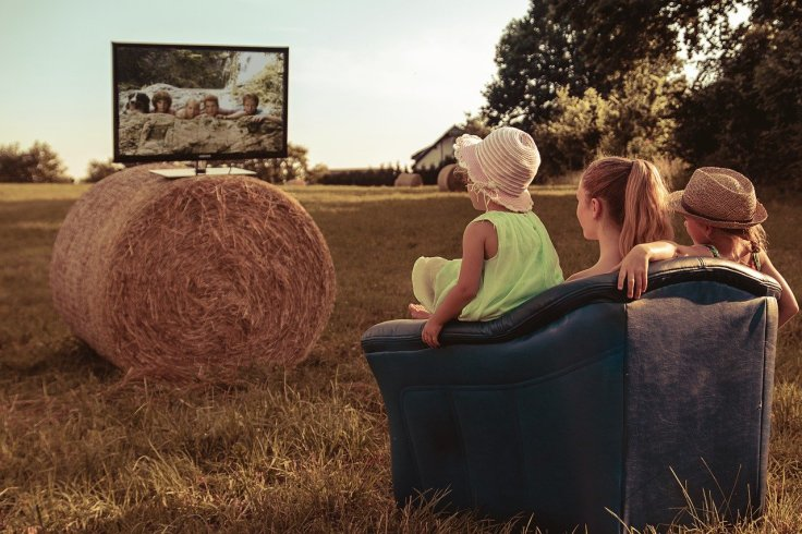Family watching TV in a field